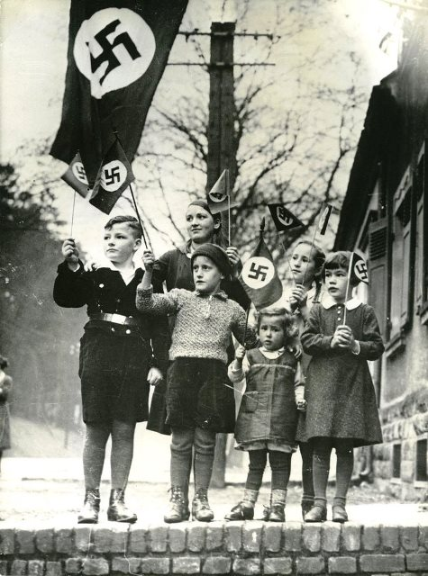 This picture is of multiple young children shown holding the Nazi flag. It represents the Nazi Youth, and how Germans had unflinching resolve for their leader, and his views. See more photos: http://cmore.pics/8SlxG